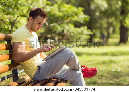 Young athlete after a hard workout, sitting on a wooden bench in a park, surfing the internet on a tablet computer