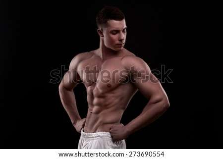 young athlete bodybuilder man isolated over black background - stock photo