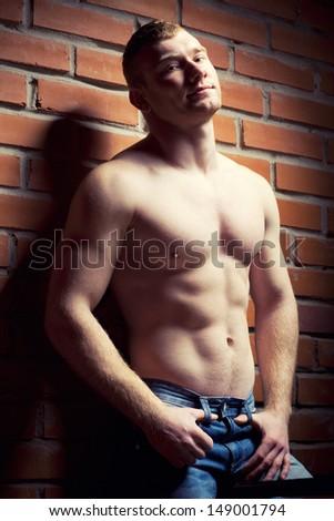 Young athlete bodybuilder man near brick wall - stock photo