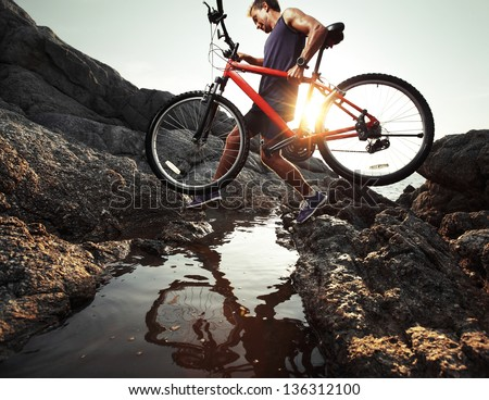 Young athlete crossing rocky terrain with bicycle in his hands - stock photo