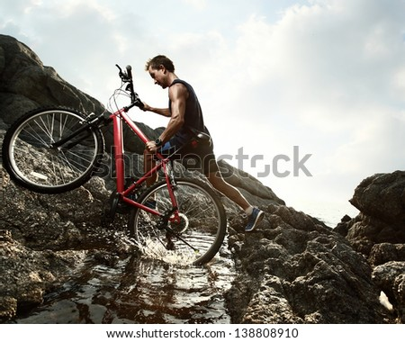Young athlete crossing water barrier with bicycle - stock photo