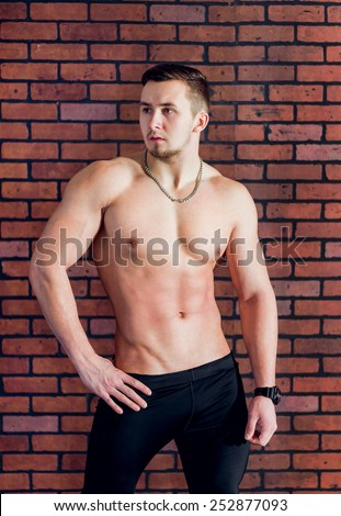 Young athlete demonstrates his beautiful, slender body standing on the brick wall background.