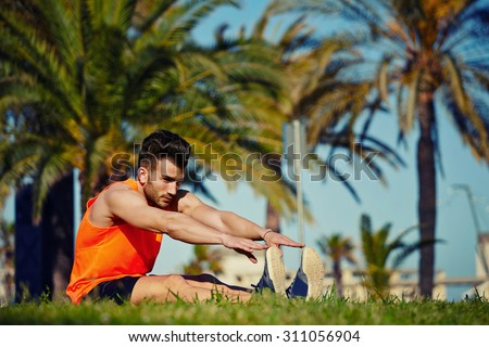 Young athlete doing physical exercises for legs while training outdoors in the park in sunny afternoon, fit handsome man warming up before begin his run while stretching legs seated on the grass - stock photo