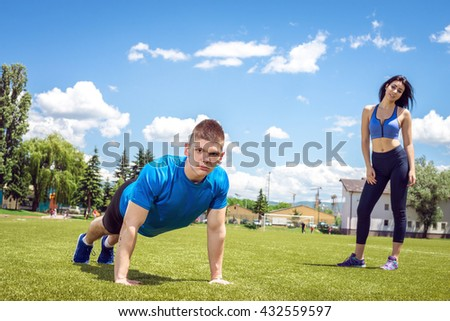 Young athlete doing push ups outdoor on grass football field together with his female partner during hot summer day. Toned image.