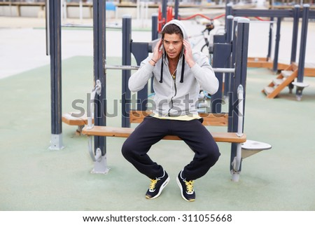 Young athlete dressed in sportswear resting tired after exercise while sitting at outdoors gym equipment, handsome sportsman enjoying a rest after workout and listening to music in headphones - stock photo