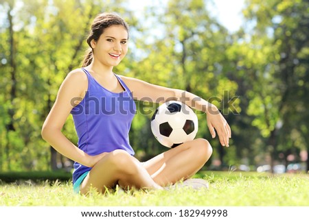Young athlete female sitting on a green grass and holding a soccer ball in a park - stock photo