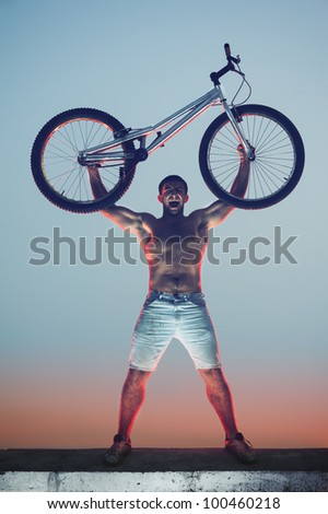 Young athlete holding his bike over his head, yelling - stock photo