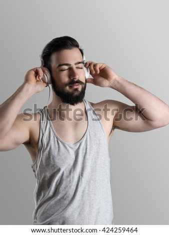 Young athlete in tank top enjoying music with closed eyes after hard workout.