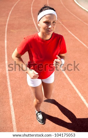 young  athlete is at the start of the treadmill at the stadium