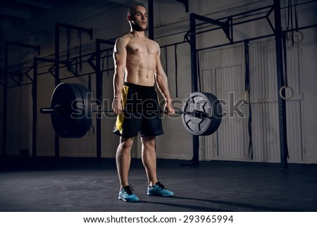Young athlete lifting barbells at gym - stock photo