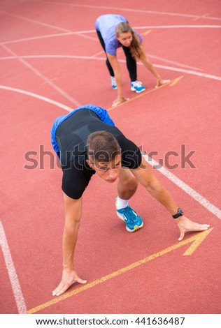 Young athlete on a running track, ready to go from starting blocks