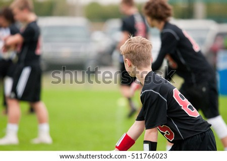 Young athlete playing 7 on 7 football boy in black and red jersey.