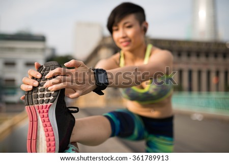 Young athlete put her leg on railing for a good stretch, selective focus