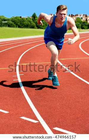Young athlete running on a red racetrack.