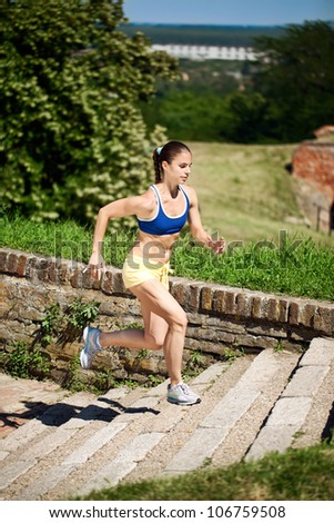 Young athlete running on stairs outdoors - stock photo
