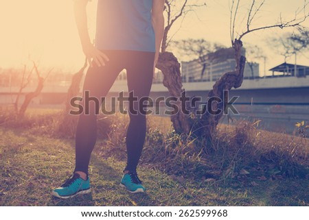 Young athlete standing in park at sunset (intentional sun glare and vintage color)