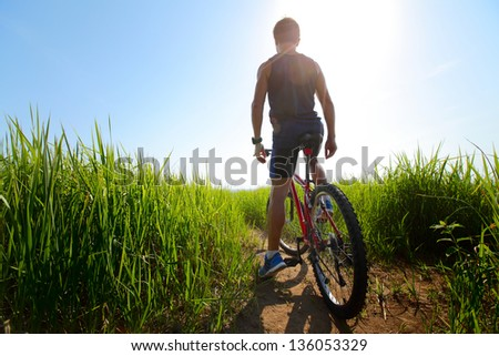 Young athlete standing with bicycle in a meadow with green lush grass