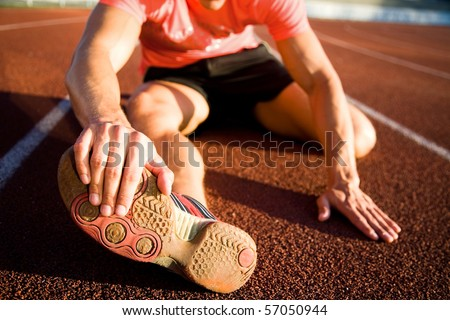 Young athlete stretching on the treadmill stadium. unrecognizable - stock photo
