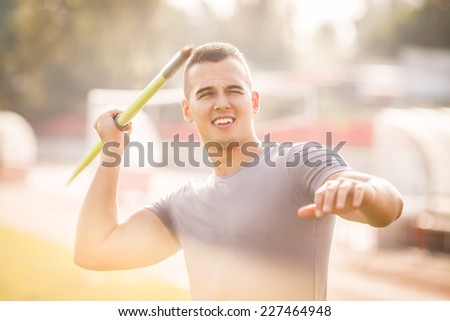 Young athlete throwing the javelin - stock photo
