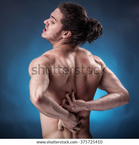 Young athlete who has a painful twinge on blue background - stock photo