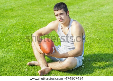 Young athlete with rugby ball sitting on grass