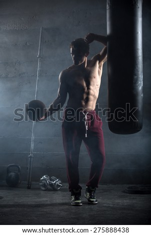 Young athlete with the ball in one hand stands near the punching bag. Snapshot in dark colors. - stock photo