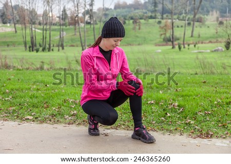 Young athlete woman hurting from a knee injury on a cold winter day in the track of an urban park. - stock photo