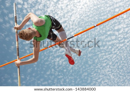 Young athletes pole vault seems to reach the sky - stock photo