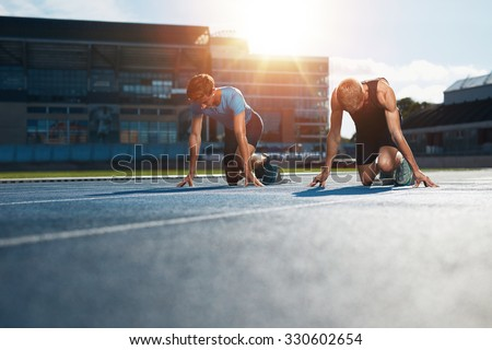 Young athletes preparing to race in start blocks in stadium. Sprinters at starting blocks ready for race with sun flare. - stock photo