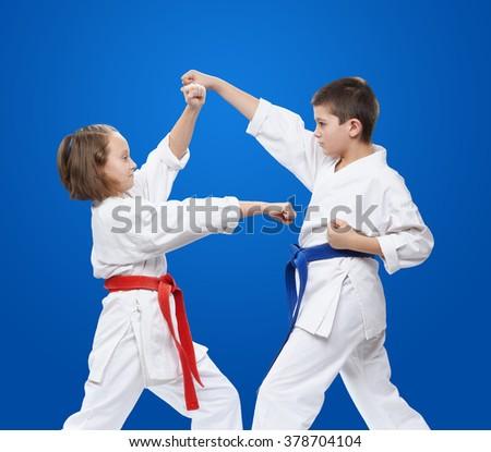 Young athletes train blocks and kicks of karate - stock photo