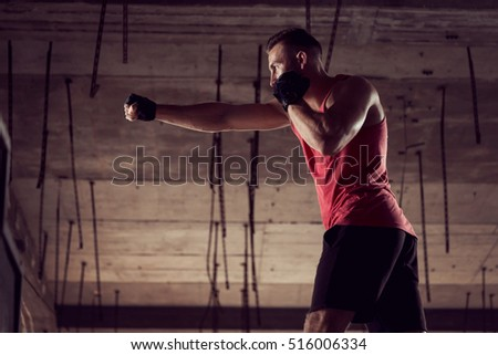 Young athletic built man working out in an abandoned building, boxing