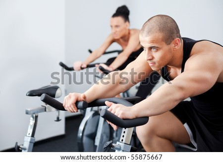 Young athletic couple in gym, male on focus