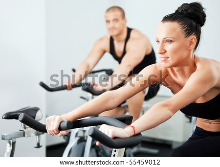 Young athletic couple on veloargometers in gym, female on focus