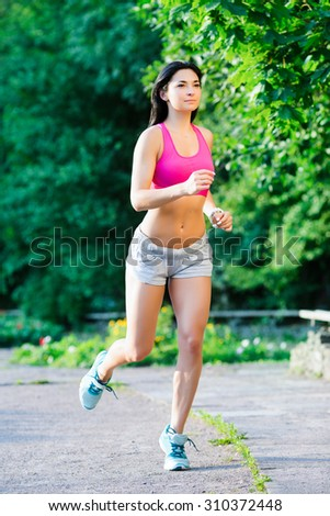 Young athletic girl, with long dark hair, wearing in a pink top and gray shorts, jogging in the green park, full body