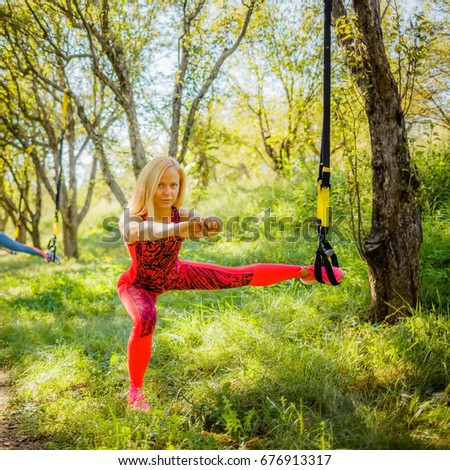Young athletic healthy blonde exudes leg exercises on a special hanging  device in a forest in