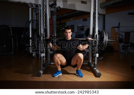 Young athletic man doing deep squats with barbell at health fitness center