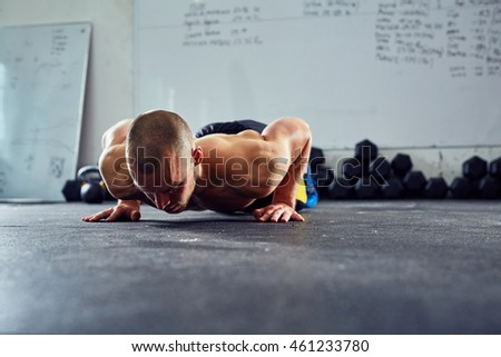 young athletic man doing push-ups exercise at the gym