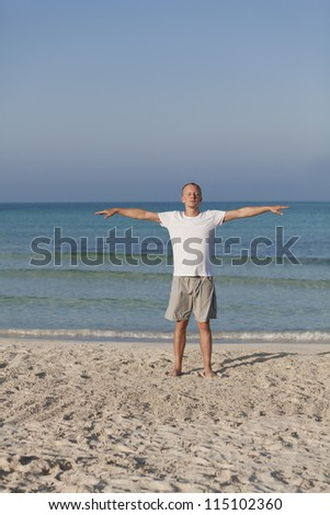 Young athletic man doing sport yoga on the beach in the sand on the beach in the sun