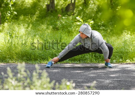 Young athletic man doing stretching exercises, outdoor. Healthy man working out in park - stock photo