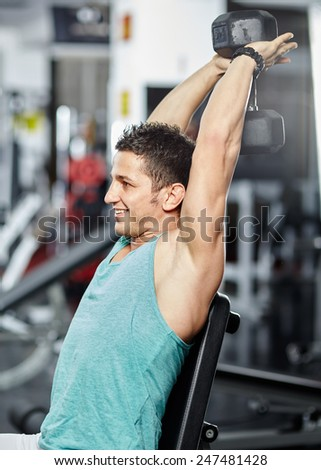 Young athletic man doing triceps and shoulder workout in a gym - stock photo