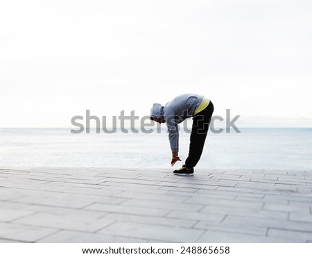Young athletic man doing warm up before a morning run outdoors, full length of a young jogger stretching in the morning on a seaside - stock photo