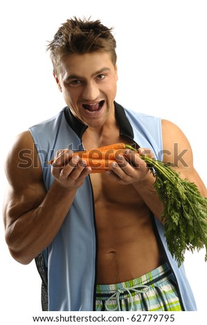 Young athletic man eating carrots - stock photo