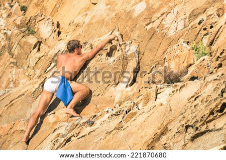 Young athletic man free climbing without equipment on dangerous rock slope - Adventurous concept of freedom and contact with wild nature - stock photo