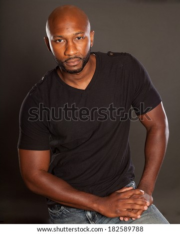 Young Athletic man in a casual pose wearing a dark t-shirt - stock photo