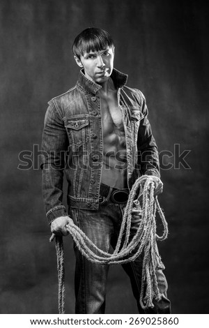 Young athletic man in jeans jacket with a rope. - stock photo