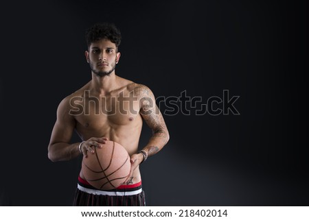 Young athletic man on dark background holding basketball ball, looking at camera - stock photo