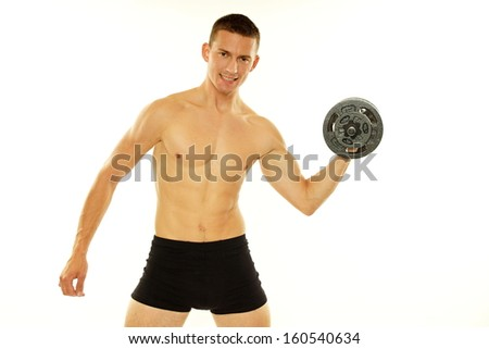Young athletic man poses with dumbbell