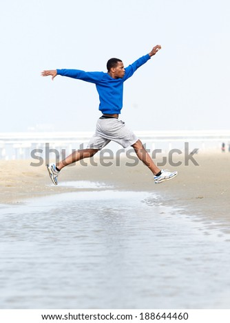 Young athletic man running and jumping at beach