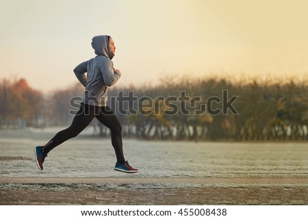 Young athletic man running at park during cold autumn morning - stock photo