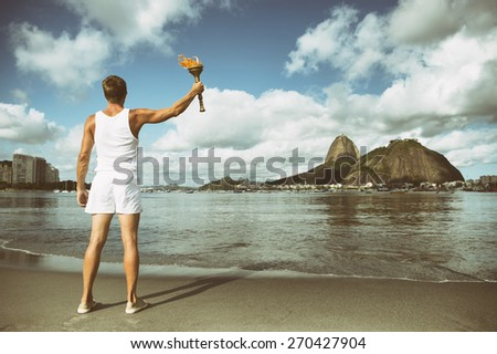 Young athletic man standing with torch against Rio de Janeiro Brazil skyline at Botafogo Bay with Sugarloaf Mountain - stock photo